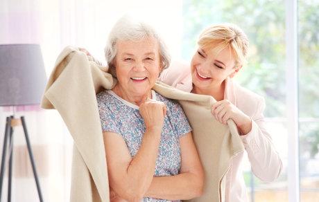 caregiver giving blanket to elder woman