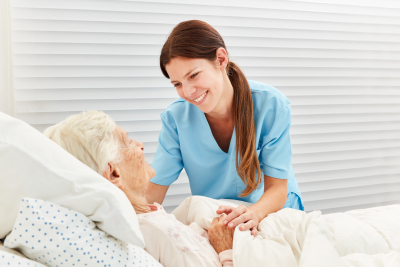 caregiver caring for elder woman in bed