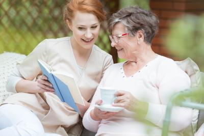 nurse reads a book to elder woman